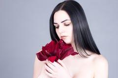 Portret die van een mooi brunette, neer met een boeket van rode bloemen kijken royalty-vrije stock foto