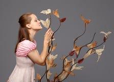 Portret die van een mooie vrouwen ruikende bloem, zich op grijze achtergrond bevinden Royalty-vrije Stock Foto