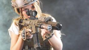 Portret die van een mooie vrouwenstrijder met vuurwapen in handen, vijand beogen Langzame Motie stock videobeelden