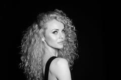 Portret die van een vrij krullende blondevrouw, zwarte kleding dragen stock afbeelding