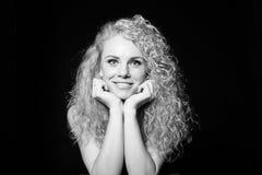 Portret die van een vrij krullende blondevrouw, zwarte kleding dragen Stock Foto