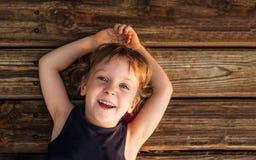 Portret die van een weinig roodharig meisje, op houten vloer liggen stock fotografie