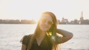 Portret die van gelukkig ontspannen Kaukasisch meisje in zonnebril die, bij camera op verbazende het strandzonsondergang van de s stock video
