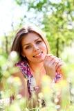 Portret die van gelukkige jonge vrouw in een weide op de warme zomer liggen stock foto's