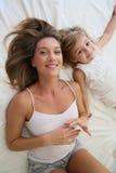 Portret die van gelukkige moeder en dochter in bed liggen stock afbeelding
