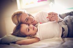 Portret die van gelukkige moeder en dochter op een bed liggen royalty-vrije stock foto