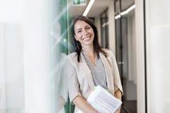 Portret die van gelukkige onderneemster zich met documenten door muur op kantoor bevinden stock fotografie