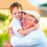 Portret die van gelukkige opa en kleinzoon in openlucht omhelzen Royalty-vrije Stock Fotografie