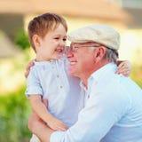 Portret die van gelukkige opa en kleinzoon in openlucht omhelzen Royalty-vrije Stock Foto