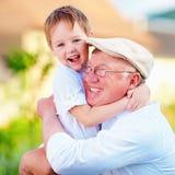 Portret die van gelukkige opa en kleinzoon in openlucht omhelzen Stock Fotografie