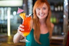 Portret die van gelukkige vrouw een cocktailglas houden bij barteller Stock Afbeeldingen