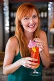Portret die van gelukkige vrouw een cocktailglas houden bij barteller Royalty-vrije Stock Afbeelding
