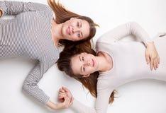 Portret die van gelukkige zusters op de vloer liggen Royalty-vrije Stock Foto's