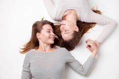 Portret die van gelukkige zusters op de vloer liggen Stock Afbeelding
