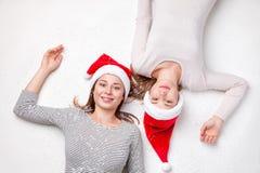 Portret die van gelukkige zusters op de vloer liggen die Kerstmishoeden dragen Stock Foto