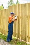 Portret die van gemiddelde lengte van arbeider houten omheining het construeren Stock Foto's
