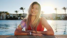 Portret die van glimlachend jong meisje, camera bekijken Mooie vrouw in rode zwempakzitting in het blauwe zwembad  stock footage