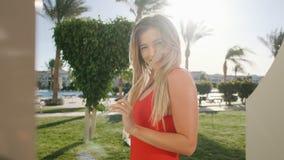 Portret die van glimlachend jong meisje, camera bekijken Mooie vrouw in rood lichaamszwempak op hete zonnige dag Ligstoel op stra stock videobeelden