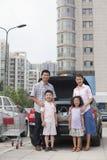 Portret die van glimlachende familie zich naast de auto met het winkelen zakken bevinden stock afbeeldingen