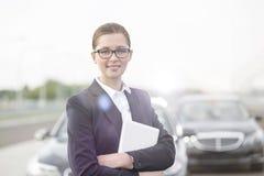 Portret die van glimlachende onderneemster zich met digitale tablet tegen auto's bevinden stock afbeelding