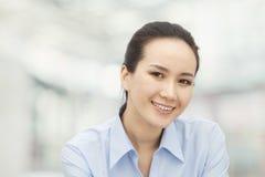 Portret die van glimlachende zekere jonge vrouw in knoop onderaan overhemd, camera onderzoeken Royalty-vrije Stock Afbeeldingen