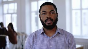 Portret die van het ernstige jonge Afrikaanse succesvolle gebaarde zakenman luisteren, formele kleding in modern zolderbureau dra stock footage