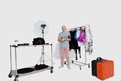 Portret die van hogere fotograaf zich voor klerenrek bevinden in studio Royalty-vrije Stock Afbeelding