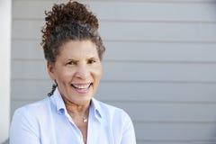 Portret die van Hogere Vrouw zich buiten Grey Clapboard House bevinden stock afbeeldingen