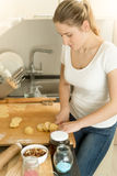 Portret die van huisvrouw deeg op keuken maken Stock Fotografie