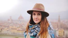 Portret die van jong mooi Kaukasisch meisje in hoed met vreedzame geheimzinnige glimlach, camera in regenachtig Florence bekijken stock video