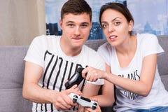 Portret die van jonge mannelijke en vrouwelijke gamers videospelletje spelen stock afbeeldingen