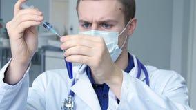 Portret die van jonge mannelijke Kaukasische arts die een vloeistof van een spuit gieten aan een buis, blauwe vloeistof in een re stock videobeelden