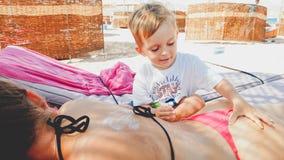 Portret die van jonge moeder op het liggen sunbed bij strand terwijl haar kindzoon die haar een massage maken royalty-vrije stock fotografie