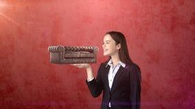 Portret die van jonge vrouw 3D leerbank op de open handpalm houden, over geïsoleerde studioachtergrond Bedrijfs concept Stock Afbeeldingen