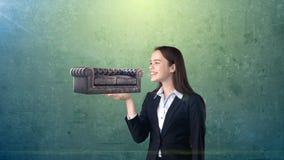 Portret die van jonge vrouw 3D leerbank op de open handpalm houden, over geïsoleerde studioachtergrond Bedrijfs concept Royalty-vrije Stock Afbeeldingen