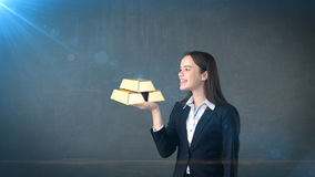 Portret die van jonge vrouw gouden bars op de open handpalm houden, over geïsoleerde studioachtergrond Bedrijfs concept Stock Fotografie