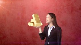 Portret die van jonge vrouw gouden bars op de open handpalm houden, over geïsoleerde studioachtergrond Bedrijfs concept Royalty-vrije Stock Afbeelding