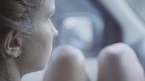 Portret die van jonge vrouw met naakte knieën die in het bewegen van auto zitten, spiegel bekijken stock videobeelden