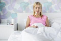 Portret die van jonge vrouw temperatuur met thermometer vergen Stock Afbeelding