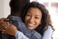 Portret die van jonge zwarte glimlachende vrouw echtgenoot omhelzen stock foto's
