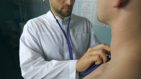 Portret die van knappe arts patiënt met stethoscoop onderzoeken Jonge medische arbeider het luisteren hartslag van zieken stock videobeelden