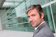 Portret die van knappe zakenman zich op voorzijde van de moderne bouw bevinden Royalty-vrije Stock Foto's
