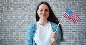 Portret die van leuk meisje Amerikaanse vlag houden en op bakstenen muurachtergrond glimlachen stock video