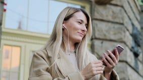 Portret die van leuk meisje in hoofdtelefoons, aan muziek luisteren en op mobiele telefoonoutddor doorbladeren Bloggerrollen door stock videobeelden