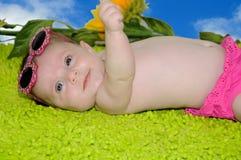 Portret die van leuke gelukkige baby, op groen tapijt liggen Stock Afbeelding