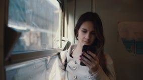 Portret die van meisje zich in de trein bevinden en smartphone gebruiken Het jonge vrouw texting sms en doorbladert Internet stock videobeelden