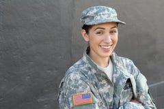 Portret die van mooi jong meisje groen militair stijljasje dragen en hoed die wapens het kruisen isoleerde op grijs royalty-vrije stock afbeeldingen