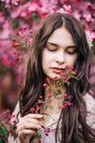Portret die van mooi meisje in een roze kleding, neer met half open lippen het kijken, houdt op hand een takje met knoppen, close Royalty-vrije Stock Afbeeldingen