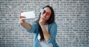 Portret die van mooi meisje selfie met de holdingslolly van de smartphonecamera nemen stock videobeelden