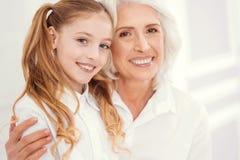 Portret die van mooie hogere dame charmante kleindochter omhelzen royalty-vrije stock afbeeldingen